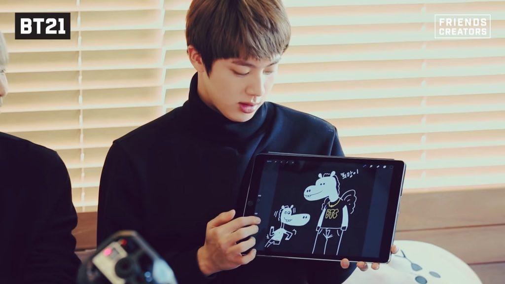 J-Hope montre une tablette avec des dessins de son personnage MANG de bt21